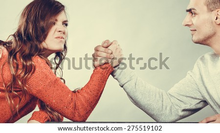 Partnership relationship concept. Girlfriend confronts his boyfriend. Woman and man arm wrestling challenge between young couple - stock photo