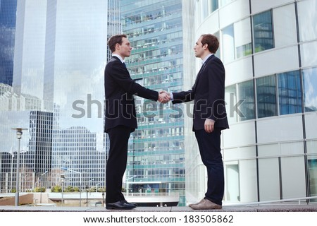 partnership, two businessman on office buildings background