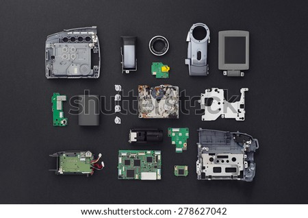 Parts of a mini DV video camera separate and well arranged over black background, above view.  - stock photo