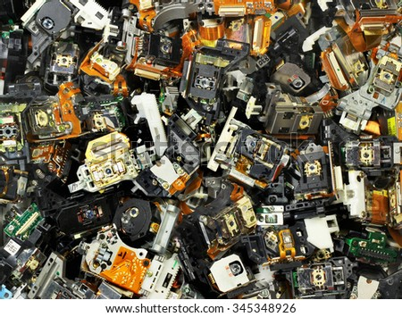 Parts of old optical drives as industrial waste background. Broken cd and dvd laser pickup units. - stock photo