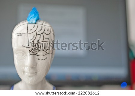 Parts of the human brain and the functions for each part. In the background there is a monitor and keyboard. Concept for brain functions and activity - stock photo