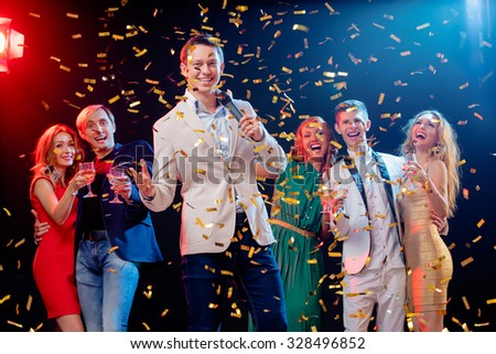 Party and celebration. Group of happy smiling friends having fun together, singing karaoke in the nightclub. - stock photo
