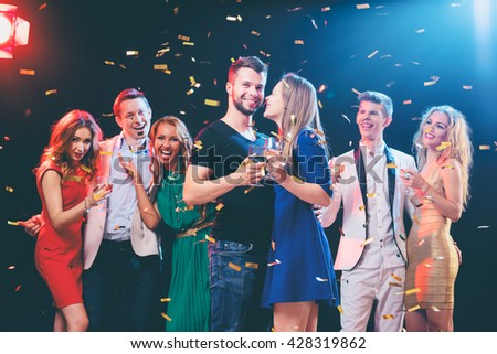 Party and celebration. Group of six happy smiling friends having fun together among confetti in night club. - stock photo