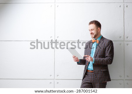 Party and technology. Cheerful young man in plaid suit and bowtie using tablet computer and smiling while standing against white wall. - stock photo
