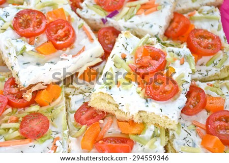party appetizer with cream cheese spread slice tomatoes, cucumbers, carrots and bell pepper on pizza crust - stock photo