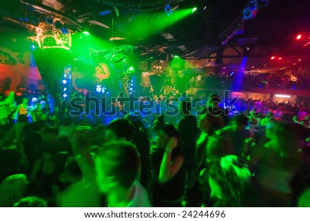 Party at Disco concert full of young people dancing in music and light show - stock photo