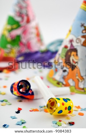 Party blowers with party hats, streamers and confetti with selective focus