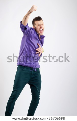 party boy screaming with hand in the air on studio background - stock photo