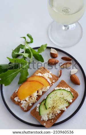 Party canapes snacks ricotta cottage cheese with sliced nectarine and cucumber and a glass of wine - stock photo