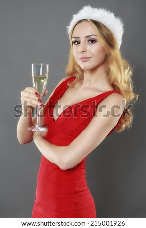 party, drinks, christmas, x-mas concept - smiling woman in red dress with a glass of champagne - stock photo