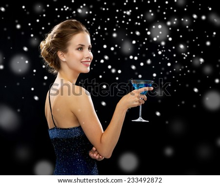 party, drinks, holidays, luxury and celebration concept - smiling woman in evening dress holding cocktail over black snowy background - stock photo
