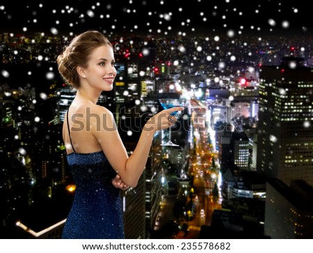 party, drinks, holidays, luxury and celebration concept - smiling woman in evening dress holding cocktail over snowy night city background - stock photo