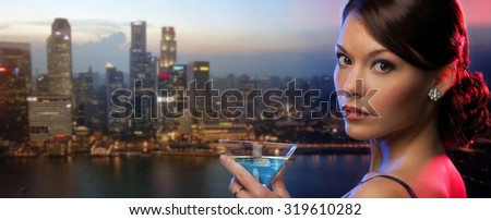 party, drinks, holidays, luxury and celebration concept - woman holding cocktail over singapore night city background - stock photo