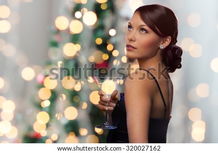 party, drinks, holidays, luxury and celebration concept - woman in evening dress with cocktail over christmas tree lights - stock photo