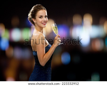 party, drinks, holidays, people and celebration concept - smiling woman in evening dress with glass of sparkling wine over night lights background - stock photo