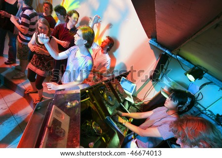 Party flock in a trendy nightclub with DJs at work and people dancing on the dance floor - stock photo