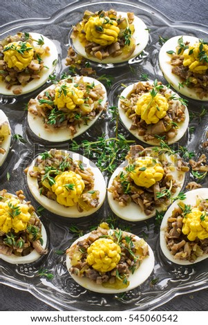 Party food: deviled eggs stuffed with mushrooms, pickled cornichons and mustard yolks. holiday recipe