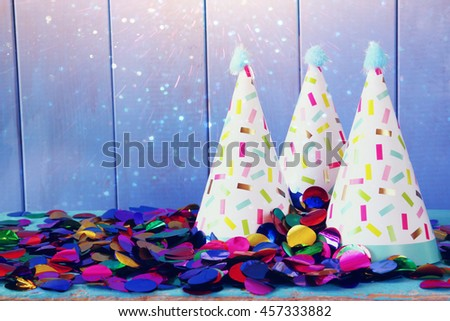 Party hat and colorful confetti on wooden table. Glitter overlay - stock photo