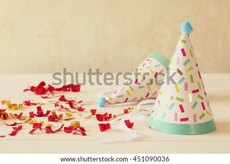 Party hat next to colorful confetti on wooden table. Top view - stock photo