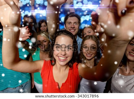 party, holidays, celebration, friends and people concept - smiling friends dancing and waving hands in club and snow effect