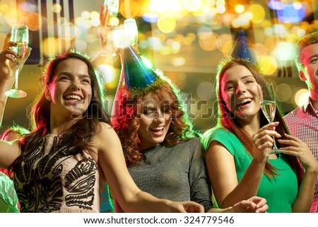party, holidays, celebration, nightlife and people concept - happy female friends in party caps with glasses of non-alcoholic champagne dancing in night club - stock photo