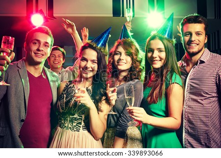 party, holidays, celebration, nightlife and people concept - smiling friends in party caps with glasses of champagne in club - stock photo