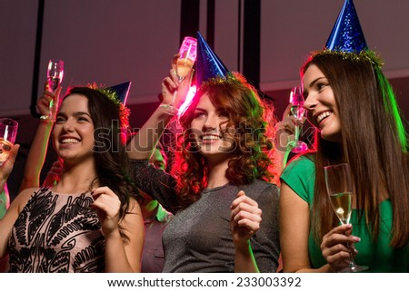 party, holidays, celebration, nightlife and people concept - smiling friends with glasses of champagne in club - stock photo