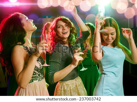 party, holidays, celebration, nightlife and people concept - smiling friends with glasses of champagne dancing in club - stock photo