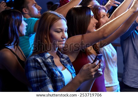 party, holidays, celebration, nightlife and people concept - smiling young woman with smartphone texting message at concert in club - stock photo