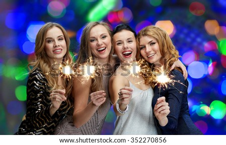 party, holidays, new year, nightlife and people concept - happy young women with sparklers over lights background