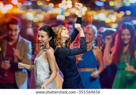 party, holidays, nightlife and people concept - happy young women dancing at night club disco over night lights background - stock photo
