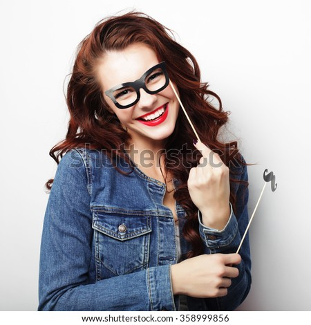 Party image. Playful young woman holding a party glasses.   - stock photo