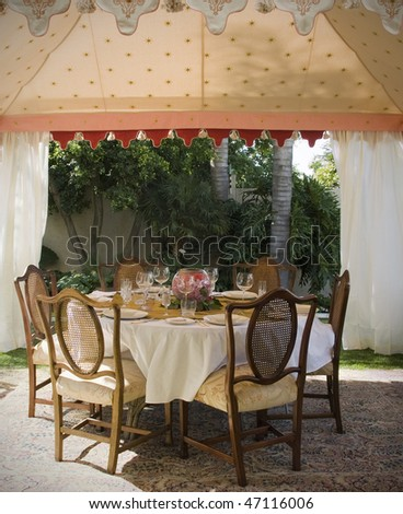 Party lunch, wedding or dinner tent in suburb garden with table and chairs - stock photo