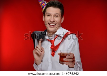 Party man. Drunk businessman in party hat standing with a glass of whiskey while isolated on red - stock photo