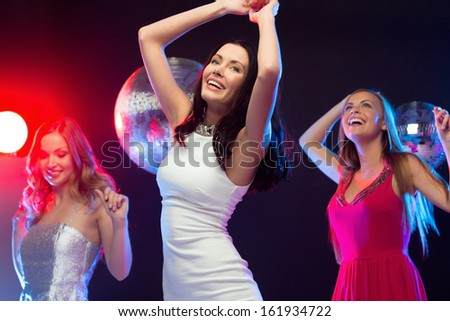 """party, """"new year"""", celebration, friends, bachelorette party, birthday concept - three beautiful women in evening dresses dancing in the club - stock photo"""
