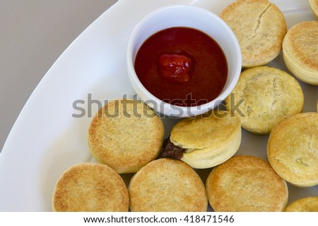 Party pies on a plate with tomato sauce. - stock photo