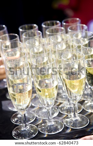 Party set of champagne flutes aligned and served in a tray - stock photo