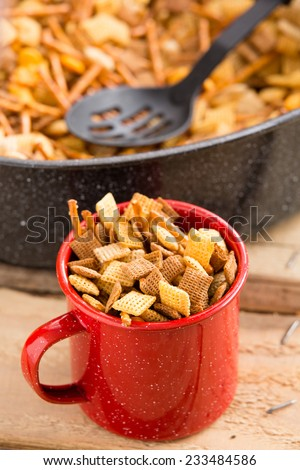 Party Snack Mix - This is a shot of a red mug filled with a holiday party mix. Shot with a shallow depth of field. - stock photo
