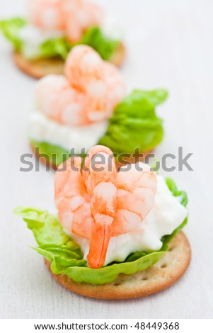 Party snacks. Prawns on a bed of lettuce, cottage cheese and savory biscuit - stock photo