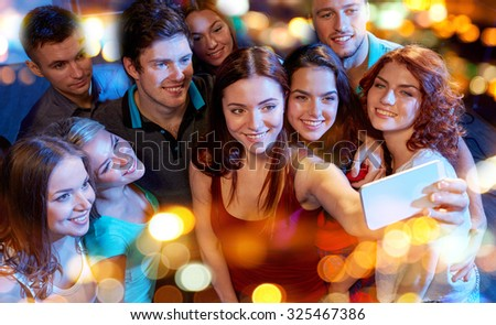 party, technology, nightlife and people concept - smiling friends with smartphone taking selfie in club - stock photo