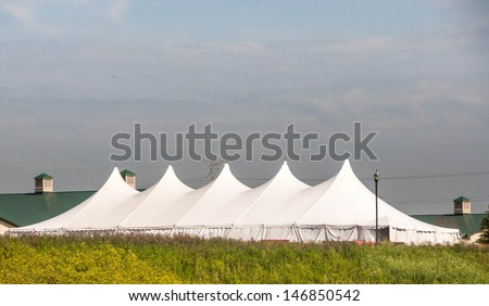 Party Tent or a big white banquet wedding tent for ceremonies. White tent against blue sky. - stock photo