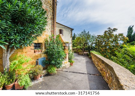 Passage between the flowers in the Italian village of medieval Tuscany. - stock photo