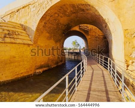 Passage under Puente Romano - Roman Bridge in Cordoba, Andalusia, Spain - stock photo