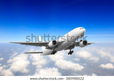 Passenger aircraft flying high above the clouds after takeoff - stock photo