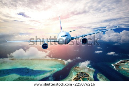 Passenger Airliner flying in the clouds - stock photo