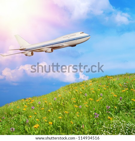 passenger airplane in the clouds against the backdrop of mountain meadow with grass and flowers. travel by air transport. flying to the top of the airliner. nobody - stock photo
