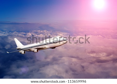 passenger airplane in the clouds at sunset or dawn. travel by air transport. flying to the top of the airliner. nobody - stock photo