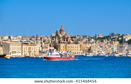 Passenger boat crosses Grand Bay, Valetta, Malta, on a bright sunny morning - stock photo