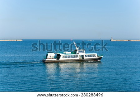 Passenger boat ferry on the sea water in the city center - stock photo