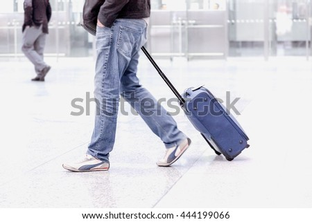 Passenger carries his luggage at the airport terminal. - stock photo